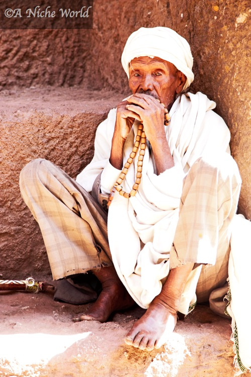 Praying with beads on the steps of Lalibela's UNESCO World Heritage rock-hewn churches