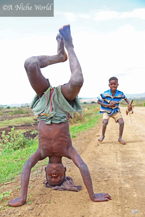 Children perform tricks along rural village roads, South Ethiopia